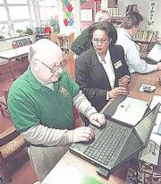 Mike Eltschinger, director of instructional computing for Lawrence Schools, works on a laptop computer as Karen Patterson-Crump of Gateway, right, demonstrates some new technology during a meeting of the district's technology committee at Hillcrest School.