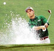 Chris DiMarco hits from a bunker on the 17th hole during the first round of the Masters. DiMarco shot an opening-round 65 Thursday at Augusta National Golf Club for a one-stroke lead.