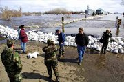 Although rains across the Northern Plains ended on Sunday, rivers kept rising. National Guardsmen and residents of Dumont, Minn., check the level of the rising West Branch Twelvemile river against the sandbag dike they had built earlier in an effort to keep flood waters from the town's business district.