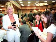 "Erin Brockovich, left, visits with Lawrence High School students Julia Seibel, senior, in red, and Carolyn Tharp, junior, after speaking at the Kansas Press Assn. annual convention at the Lawrence Holidome. Brockovich, a Lawrence native, was thrust into the limelight when her research for a California law firm became the subject of the feature film ""Erin Brockovich,"" starring Julia Roberts."
