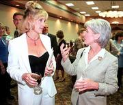 Lawrence native Erin Brockovich, left, speaks with Kansas Insurance Commissioner Kathleen Sebelius during a reception at the Kansas Press Assn. annual convention at the Lawrence Holidome.