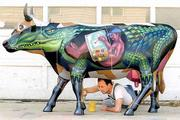 "Lawrence muralist David Loewenstein puts the finishing touches on ""Co-Walligator,"" his entry in Kansas City&squot;s CowParade 2001. Loewenstein says his creation is ""an alligator who has, in a very rudimentary way, disguised himself as a cow."" The other side of his cow art is shown in the ""parade"" at the top and bottom of this page."