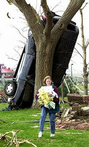 Cindy Deutsch salvages items from her aunt's house, which was destroyed by Saturday's tornado. Behind Deutsch is her aunt's Chevy Tahoe.