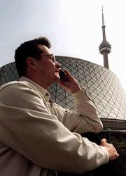 Canada is considering relaxing laws on jamming devices to allow such places as theatres, restaurants, libraries, hospitals and private companies to cut off cell phone transmissions on their property. Here, Dmitri Lopatine calls his wife on his cell phone outside of Roy Thomson Hall in Toronto, one locale that would likely use such a device.