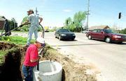 A storm-related electrical short necessitated repair work to the traffic signals at 15th Street and Kasold Drive. On Tuesday, Travis New, left, and Bob Johnson Electric of Topeka help feed some new wire to repair the damage.