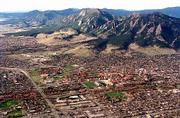 The needlesharp Flatirons form a mountain backdrop for Boulder, Colo., a cosmopolitan city with a population of more than 95,000 people. City and county efforts to purchase and preserve open space have enabled Boulder to save wildlife habitat, agricultural lands and their mountains from development. This view shows the Flatirons to the southwest at top of frame with protected green space below. Just below center at right is the University of Colorado.