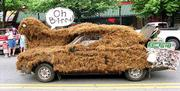 """The entry """"Oh Bird-Snuffy"""" makes its way through downtown Lawrence during last year&squot;s Art Tougeau parade. """"Oh Bird"""" was sponsored by the Peer Support group of Independence Inc. and featured a car covered in oak tree mulch and a trunk full of garbage."""
