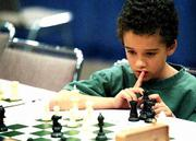Nicky Henriquez, a first-grader at Quail Run School, ponders his next move during the United States Chess Federation's Supernationals tournament. Henriquez is one of 40 Lawrence students competing this weekend in the national contest in Kansas City, Mo.