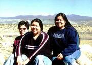 Haskell Indian Nations University students, from left, Tracy Kennedy, Jessica Youngbird and Ashley Youngbird rest after taking a hike on a mesa near Acoma Pueblo. In the background is Mount Taylor.