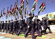 Iraqi Air Force academy students carry Iraqi and Palestinian flags during a celebration of Saddam Hussein's 64th birthday, in his hometown of Tikrit, Iraq. The event was Saturday.