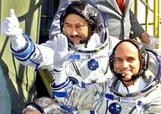 Cosmonaut Talgat Musabaev, top, and American space tourist Dennis Tito, bottom, wave as they board the Soyuz rocket for a journey to the international space station. They blasted off Saturday from the Baikonur cosmodrome in Kazakhstan.