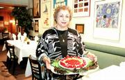 A tasty dessert made up of a cheesecake filling topped with fresh strawberries and pineapple is a summer seasonal treat at Fifi's Restaurant, as displayed by owner Fifi Nabil.