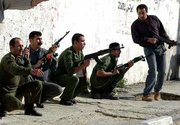 Palestinian police officers take cover after Israeli forces rocketed their headquarters Thursday in Gaza City.