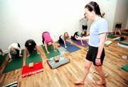 Yoga instructor Margaret Carr encourages first-time students through a challenging stretch. Carr is a certified yoga instructor and has traveled to India to study the craft.