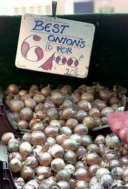 "A sign advertising the price of onions is seen with an incorrect apostrophe added to the word ""onions"" in Maida Vale, London."