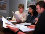 "Eileen Marolla, a mortgage loan officer with Philadelphia Financial Mortgage Co., guides first-time home buyers Sindhu Cherian and David Schutte through the mortgage process. Marolla said many people are seeking advice on whether to refinance their home loans because of the weak economy. She said her customers are waiting to jump on a 30-year fixed-rate loan with interest below 7 percent and no ""points."" She cautions that the mortgage market&squot;s bottom remains difficult to predict."