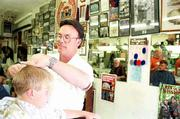 Mike Amyx, right, maintains a large display of sports memorabilia, which adorn the walls of the Amyx Barber Shop, 842 1/2 Mass.
