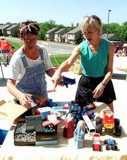 Kara Perry and Allison Langwell sort through items at a multifamily garage sale.
