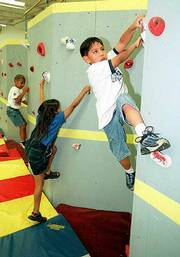 Clinging to the new rock climbing wall at Broken Arrow School, first-grader Jordan Yeahpau, right, demonstrates his skills during physical education class.