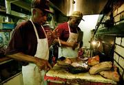 "High-fat, high-cholesterol red meat is such a staple of the Midwestern diet that the region is known in health circles as the ""Coronary Valley."" Here, Quincy Echols, left, and Willis Simpson prepare a barbecue special at Arthur Bryant&squot;s restaurant in Kansas City, Mo. Echols says, ""It&squot;s so good you don&squot;t think about the high cholesterol."""