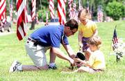 Memorial Day, while designated for remembering fallen veterans of the armed services, also is a day for decorating graves of loved ones. Monday, Steve Ryan, his son Noah and daughter Cecilia, planted flowers at Steve's grandparents' grave at Memorial Park Cemetery. The family drove from Leawood to the Lawrence cemetery.