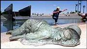 "The sculpture ""Death on Shore"" depicts a fallen soldier and includes a pack with a Bible and letters spilled onto the beach. At right, Lawrence sculptor Jim Brothers wades through the water to the beach."