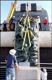 """Scaling the Wall"" a story wall depicting four WWII Ranger soldiers climbing Pointe Du Hoc at Normandy, France on D-Day, is lifted into position at the National D-Day Memorial in Bedford, VA. The memorial and statuary will be dedicated Wednesday, June 6, 2001, the 57th anniversary of the invasion."