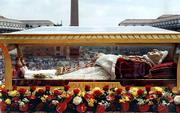 The body of Pope John XXIII is carried in a procession led by Pope John Paul II at the Vatican. John XXIII, who was pope from 1958 to 1963, was carried Sunday in a half-ton, shatter-proof coffin, dressed in a white lace over-tunic, red velvet cape and a red hat trimmed with ermine.