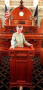 Janet Jones, chief clerk of the Kansas House of Representatives, demonstrates the new, adjustable lectern in the House chambers at the Statehouse. The lectern was recently purchased for use in the House chambers for a price of $9,437.