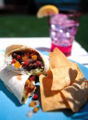 A grilled sausage burrito With tomatoes, peppers and black beans.