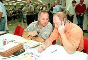 Officials with the Lawrence-based Farmers Cooperative Assn. are determining whether they'll accept bids for properties sold at a bankruptcy auction. Overland Park attorney Robert Laing, left, and Wayne Gray check their figures during the auction Thursday at the Douglas County 4-H Fairgrounds.