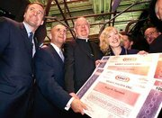 Receiving oversized stock certificates for Kraft Foods' giant initial public offering are Roger Deromedi, left, co-CEO of Kraft Inc.; Richard Grasso, New York Stock Exchange chairman; Cardinal Edward Egan, Archbishop of New York; and Betsy Holden, co-CEO of Kraft Inc. Shares of Philip Morris Cos.' Kraft Foods division, spun off Tuesday in an $8.7 billion IPO that was the second largest ever in the United States, rose 3 percent Wednesday morning as they began trading on the New York Stock Exchange.