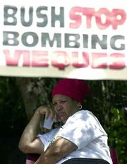 The U.S. Navy's continuation of bombing exercises on the Puerto Rican island of Vieques is spurring protests. Tuesday, activist Nayda Bermudez kept an eye on the main entrance to the U.S. Navy Camp Garcia. At least 30 demonstrators were arrested Tuesday for trespassing into the camp where the Navy has resumed military exercises using dummy bombs.