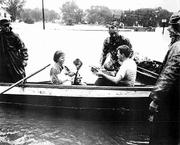 Barbara Crews cradles her infant son, Chip, as she and her husband, Ray, are evacuated from their North Lawrence home. Gib Francis, standing behind boat at left, helped get them to safety. Steve Randall, an unrelated child, was also evacuated by boat. The man at right is unidentified.