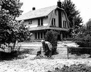 A month after the mid-July flood, A.B. Ewing shovels the dried mud and sand that covers his once-beautiful lawn. The high-water mark is evident on the side of his house, just under the first-floor windows.