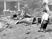 "Mud to the top of her boots, an unidentified woman comes home to wreckage, her mud-covered furniture strewn across the front lawn. The Red Cross mobilized quickly to help flood victims. A July 17, 1951, newspaper report quoted a Red Cross official as saying that ""persons will have homes and furnishings replaced on a scale approximating their previous standard of living."""