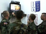 U.S. soldiers, members of the NATO-led peacekeeping troops in Bosnia, watch a live TV broadcast of former Yugoslav President Slobodan Milosevic's arraignment before the U.N. War Crimes Tribunal in The Hague, Netherlands. The soldiers watched the broadcast Tuesday in the U.S. stabilization force base near the Bosnian town of Tuzla.