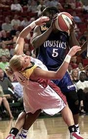 Seattle's Michelle Marciniak falls after making contact with Washington's Tausha Mills. The Mystics needed four overtimes to defeat the Storm, 72-69, Tuesday night in Seattle.