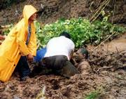 Rescuers pull survivor Cris Cuyao, right, out of the mud after a landslide in Baguio city, in northern Philippines, at the height of Typhoon Utor's fury. Cuyao survived Wednesday's landslide, but his wife was killed.