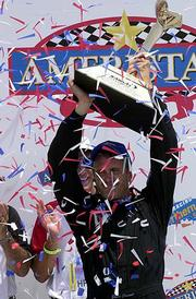Eddie Cheever Jr. hoists the Ameristar Casino Indy 200 trophy after beating IRL points leader Sam Hornish Jr. on Sunday at Kansas Speedway. An estimated 70,000 fans attended the first IRL event at the Speedway.