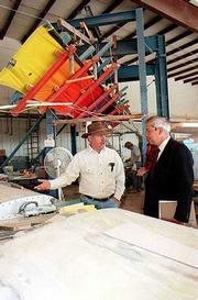 John Hunter, managing member of Lawrence-based DreamWings LLC, left, meets with Pablo Amor, an official with the European Union, during Amor's 1998 visit to the company's hangar at Lawrence Municipal Airport. The ultralight aircraft wings on display never made it to commercial production, and last week Hunter filed a Chapter 11 bankruptcy case for his company, citing at least $1.4 million in liabilities.
