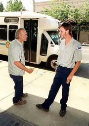 Lawrence bus system workers will vote in August to decide whether to join the Amalgamated Transit Union. Quentin Grandstaff, right, a driver for MV Transportation, is helping spearhead the union drive. Grandstaff took a break Tuesday afternoon with fellow driver Richard Weeks, left, near Ninth and Massachusetts streets.