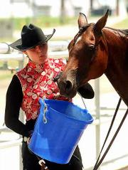 "Allison Mundy, Stillwell, tries to cool down her Arabian horse, ""Comarah,"" in the scorching heat at the Douglas County 4-H Fairgrounds. Mundy and other area horsemen were competing Tuesday to qualify for the Kansas State Fair in Hutchinson in September."