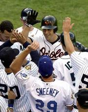 Baltimore's Cal Ripken Jr., center, accepts congratulations after hitting a solo home run in the third inning of Tuesday night's All-Star game in Seattle. The 40-year-old Ripken became the oldest player to hit a home run in an All-Star game.