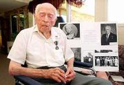 Clarence Rusk, 104, Baldwin, is one of the few remaining veterans of World War I. He celebrated his birthday Wednesday at the Baldwin Care Center by sharing stories about living in Oklahoma in the late 1800s. Childhood pictures of Rusk, along with military photos, adorn a board behind him.