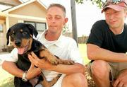 A rottweiler puppy named Rah is back home with his owner, Aaron Wright, left, after Wright's friend Paul Nuzum, right, helped search for the dog. Rah was stolen from Wright's truck Sunday night. Wright and Nuzum posted fliers and sent out thousands of e-mails to help locate the dog, which was eventually returned.