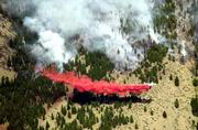 A firefighting plane drops a load of retardant on the edge of a fire in the North Cascades near Carlton, Wash. Four firefighters were killed and four others injured Tuesday in another fire, one of three burning in the North Cascades.