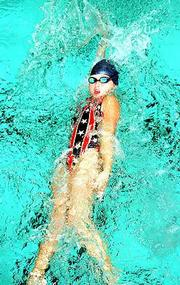 Cora Powers, 10, of Oolathe, competes in the 50-meter backstroke in the Roger Hill Invitational swim meet on Saturday at the Lawrence Indoor Aquatic Center.