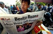 A street vendor in Jakarta reads a newspaper that proclaims Megawati Sukarnoputri as the new president of Indonesia. Megawati was sworn in as head of state on Monday, minutes after the national assembly dismissed President Abdurrahman Wahid.
