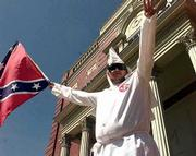 Ku Klux Klan member Alan Schmidt waves a Ku Klux Klan flag during a rally at the Hardin County Court House in Elizabethtown, Ky., in this April 28, 2001, file photo. Since the rally in Elizabethtown, some Kentucky communities have approved or are considering local ordinances that forbid public demonstrators to wear masks or hoods that conceal their faces.